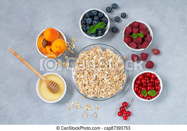 Ingredients for healthy breakfast. Oatmeal, honey with bowls of fresh summer fruits and berries: Apricot, Blueberry, Raspberry, Red Currant - csp87393753