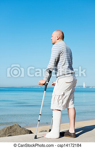 Injured Man with Crutches at sea side - csp14172184