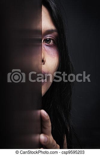 Injured woman hiding in dark - csp9595203