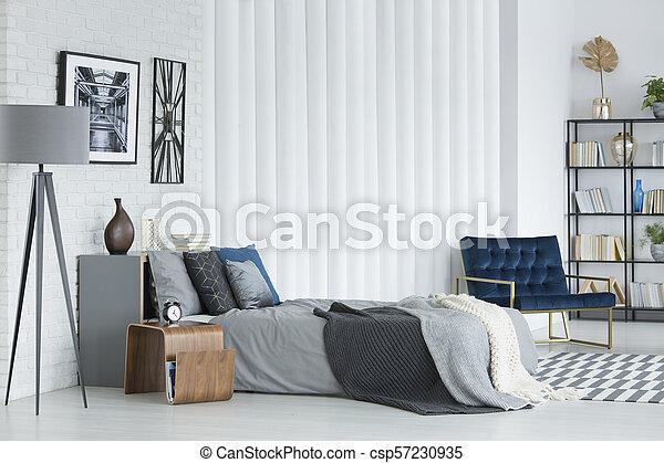 Graues Schlafzimmer Mit Sessel Graue Lampe Neben Dem Bett Gegen Weisse Wand Mit Poster Und Uhr Im Schlafzimmer Innenraum Mit Canstock