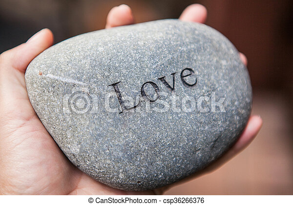 Inner balance concept: hands holding stones with the word love - csp36266376