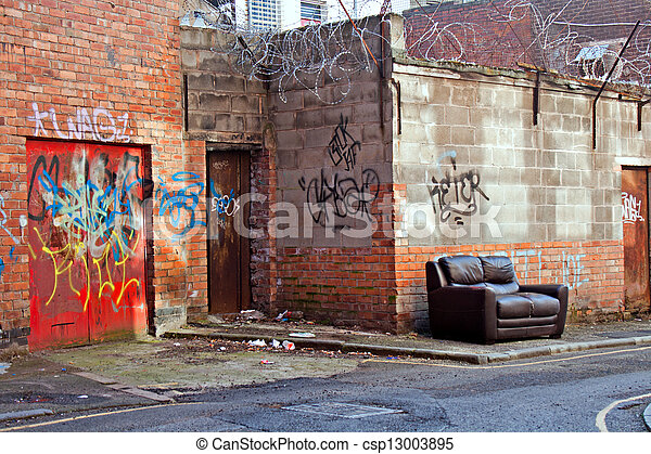 inner city dereliction abandoned couch in inner city graffiti