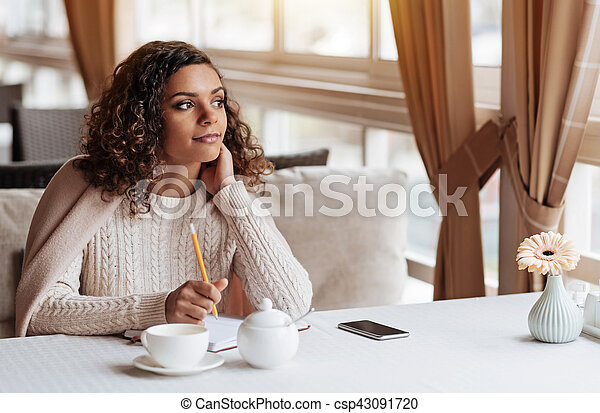 Inspired writer making notes in the cafe - csp43091720