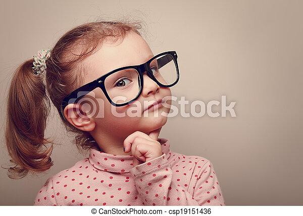 Una niña con gafas que se ve feliz. Retrato de efecto instagram - csp19151436