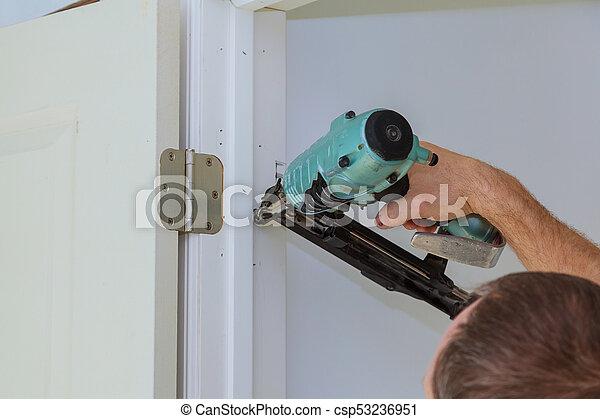 Carpenter Brad Using Nail Gun Installing New Interior Door Close Up
