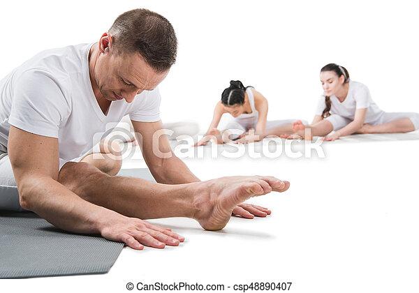 instructor doing head to knee pose janu shirshasana with
