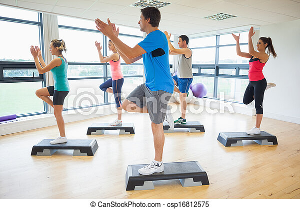 Instructor with fitness class performing step aerobics exercise - csp16812575