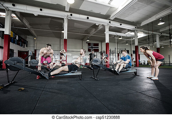 c4dd9363b0b Instructors motivating clients exercising in gym. Male and female ...