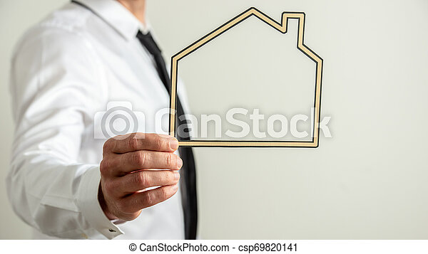 Insurance agent holding a paper cut frame of a house - csp69820141
