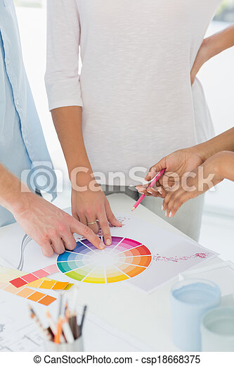 Interior designer showing colour wheel to two customers - csp18668375