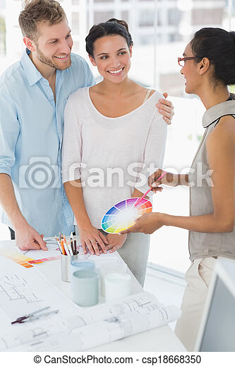 Interior designer showing colour wheel to happy clients - csp18668350