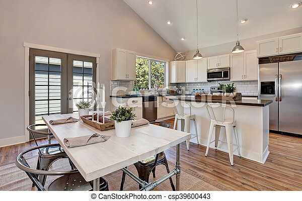Interior Of Kitchen And Dining Room With High Vaulted Ceiling White Kitchen Cabinetry And Steel Appliances Dining Table Canstock