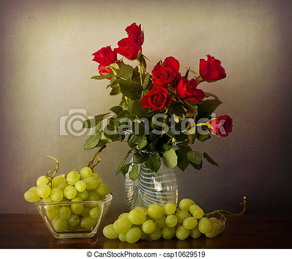 Interior retro with red roses on a glass vase, and grapes on a wooden table in chiaroscuro - csp10629519
