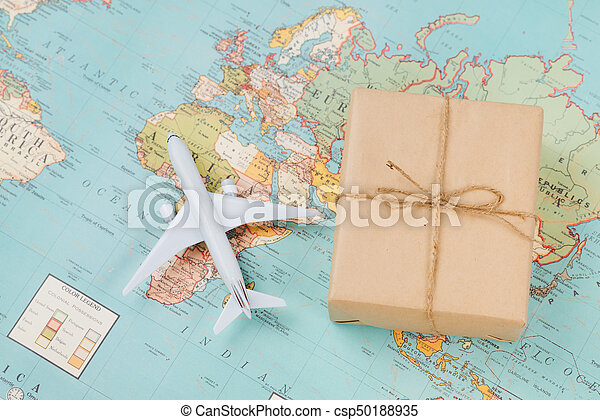 International shipping. White model airplane land on the geographical map background - csp50188935