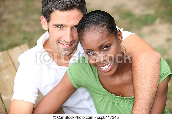 Interracial couple in a park - csp8417345