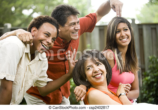 Interracial family making silly gestures posing for photograph - csp2402817