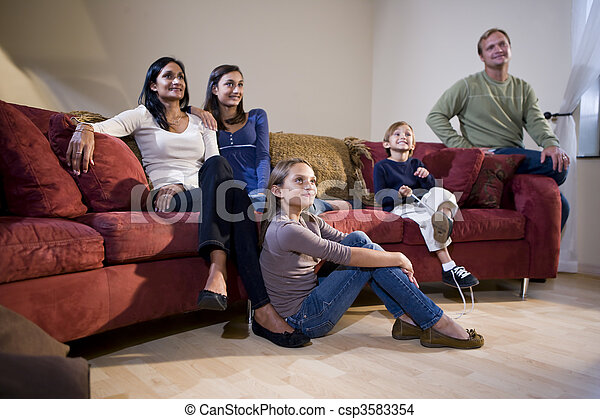 Interracial Family Sitting On Living Room Couch Watching TV   Csp3583354