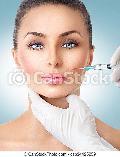 La mujer bella recibe inyecciones faciales - csp34425259