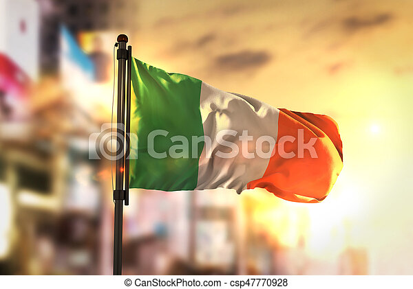Ireland Flag Against City Blurred Background At Sunrise Backlight - csp47770928