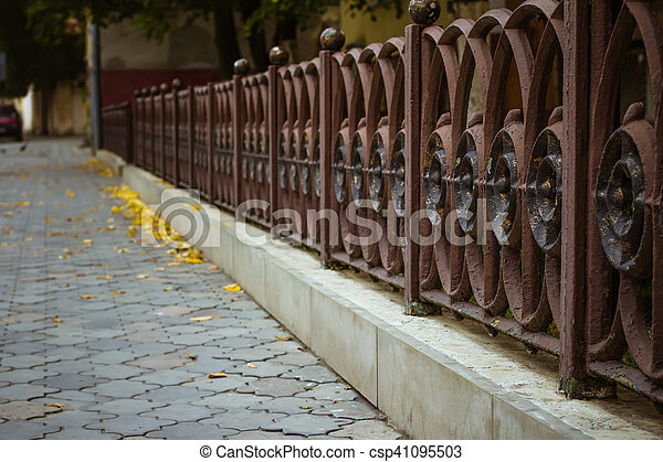 Iron fence near the sidewalk - csp41095503
