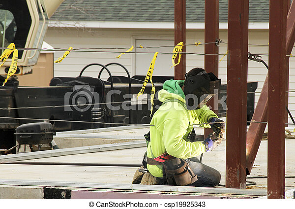 iron worker welds beams - csp19925343