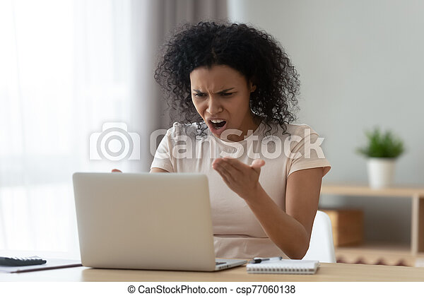 Irritated woman swears at broken or hanging out computer - csp77060138