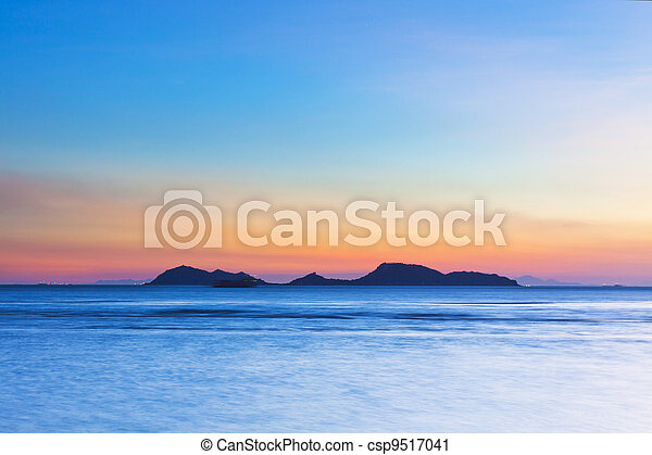 Island at sunset over the ocean - csp9517041
