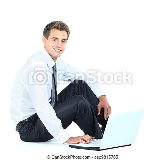 Isolated seated young businessman using a laptop - csp9815785