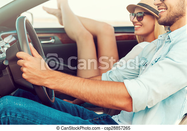 It is so good to get away out of the city. Happy young woman relaxing on the front seat while her boyfriend sitting near and driving convertible  - csp28857265