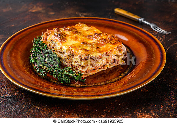 Italian Lasagne with tomato bolognese sauce and mince beef meat on a rustic plate. Dark background. Top view - csp91935925