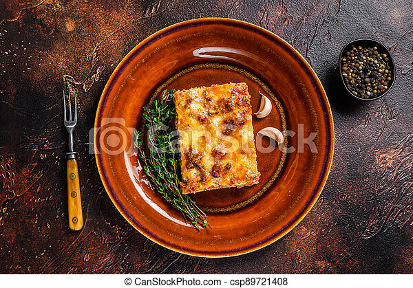 Italian Lasagne with tomato bolognese sauce and mince beef meat on a rustic plate. Dark background. Top view - csp89721408