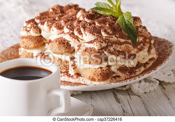 Italian Tiramisu cake on a plate and cup of black coffee close-up. Horizontal & Italian tiramisu cake on a plate and cup of black coffee close-up ...