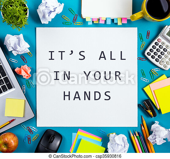 It's all in your hands. Office table desk with supplies, white blank note pad, cup, pen, pc, crumpled paper, flower on blue background. Top view - csp35930816