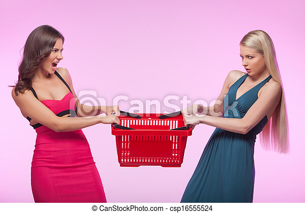 It?s mine! Two angry young women trying to take away one shopping basket while isolated on pink background - csp16555524