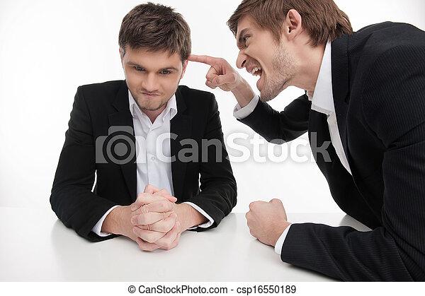 Es tu error. Joven hombre de negocios enojado señalando a otros hombres en ropa formal mientras están aislados sobre el blanco - csp16550189