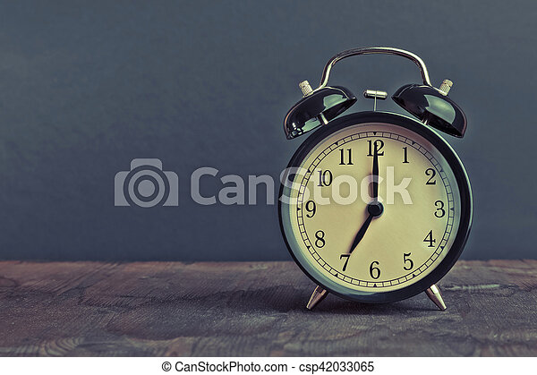 it's seven o'clock already, time to wake up for breakfast, vintage old black metallic alarm clock - csp42033065