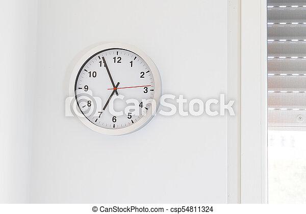 it's seven o'clock already, time to wake up for breakfast, modern white metallic alarm clock on modern white wall background - csp54811324