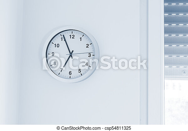 it's seven o'clock already, time to wake up for breakfast, modern white metallic alarm clock on modern white wall background - csp54811325