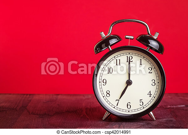it's seven o'clock already, time to wake up for love, vintage old black metallic alarm clock on red background - csp42014991