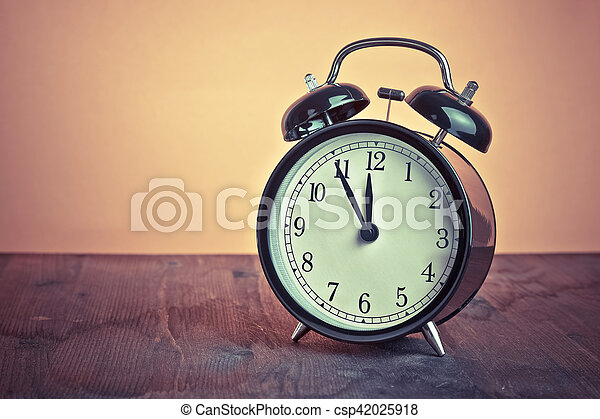 it's twelve o'clock already, time to wake up for lunch, vintage old black metallic alarm clock - csp42025918