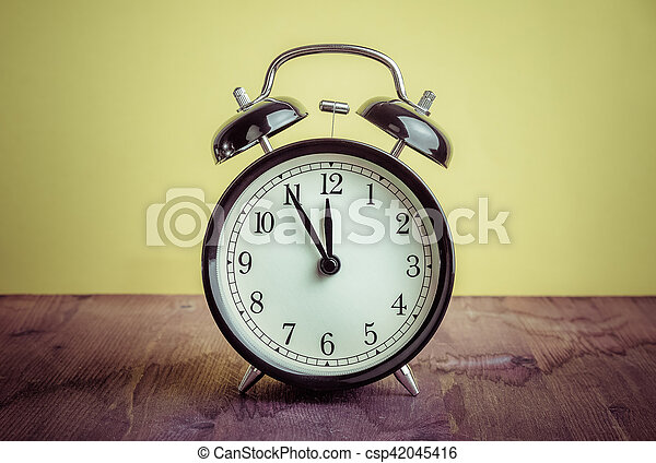 it's twelve o'clock already, time to wake up for lunch, vintage old black metallic alarm clock - csp42045416