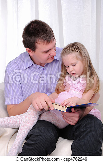 The Little Girl Is Sitting On The Lap Of His Father And Reads With Him A Book Canstock