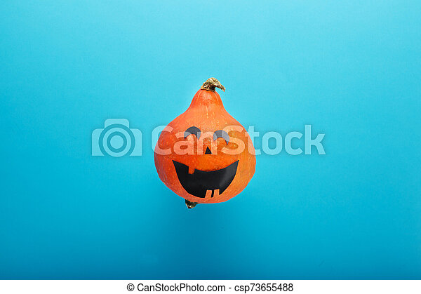 jack-o'-lantern on blue background. Happy Halloween party invitation, celebration. Halloween decorations concept. Flat lay, top view, copy space. - csp73655488