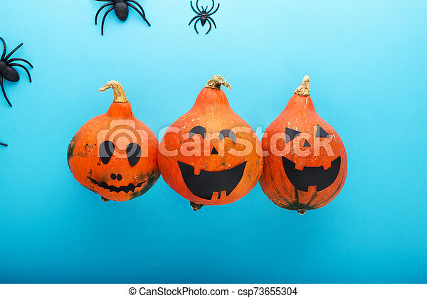 jack-o'-lantern with spiders on blue background. Happy Halloween party invitation, celebration. Halloween decorations concept. Flat lay, top view, copy space. - csp73655304