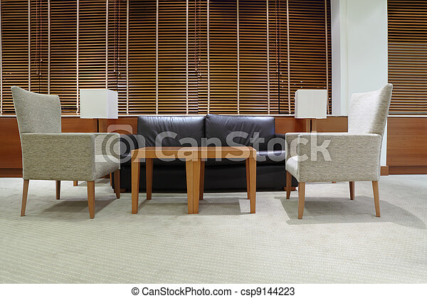 Sofa, sillones y mesa en la luz, limpia y vacía oficina, jalousie en las ventanas - csp9144223