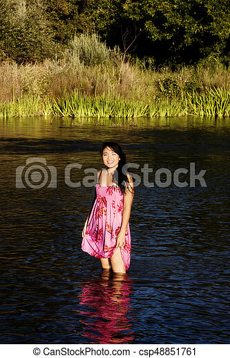 Japanese American Woman Standing In River Wearing Dress - csp48851761