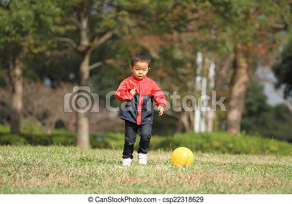 Japanese boy kicking a yellow ball - csp22318629