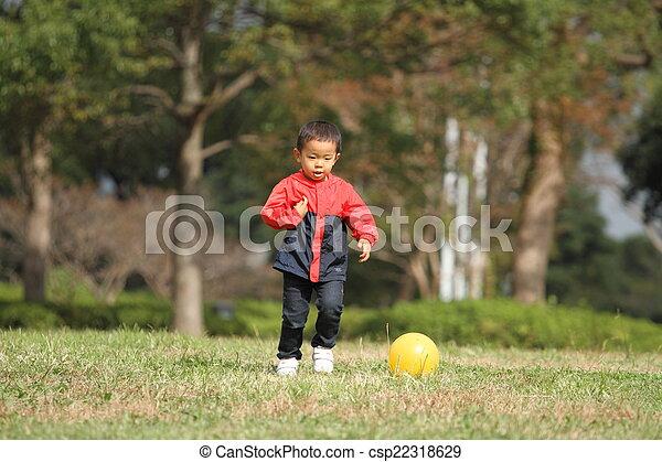 Japanese boy kicking a yellow ball - csp22318629