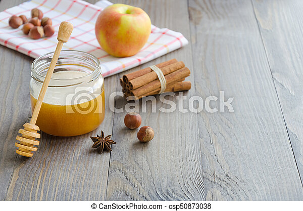 Jar of honey, honey stick, cinnamon, hazelnuts and red apple - csp50873038