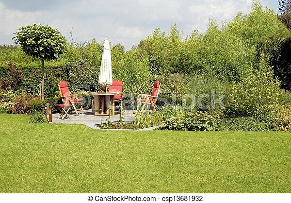 Cenar con sillas y sombrillas en un exuberante jardín - csp13681932